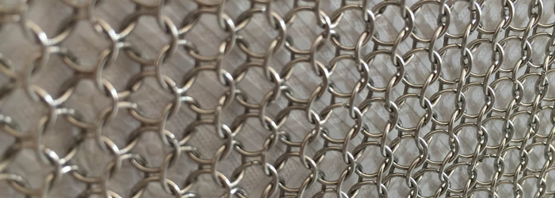 Stainless steel chain braid ring mesh  against a wooden wall