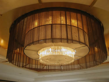 Metal coil drapery is surrounding the hotel lamp.