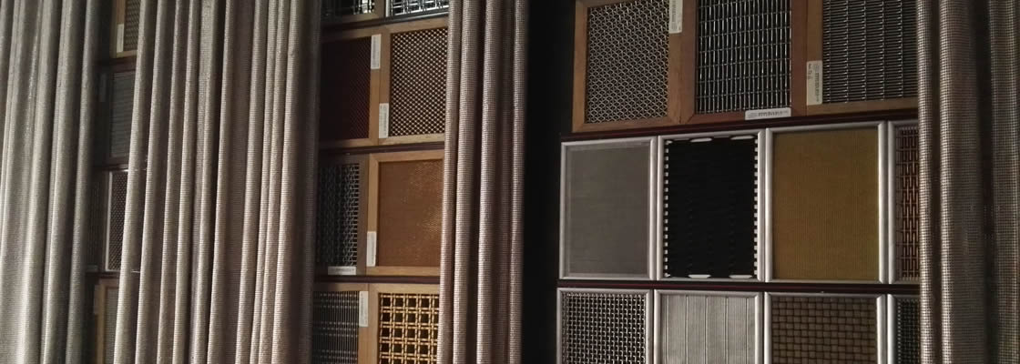 Many pieces of rectangular architecture mesh are shown on the wall and beside the samples, there is a metallic fabric curtain.